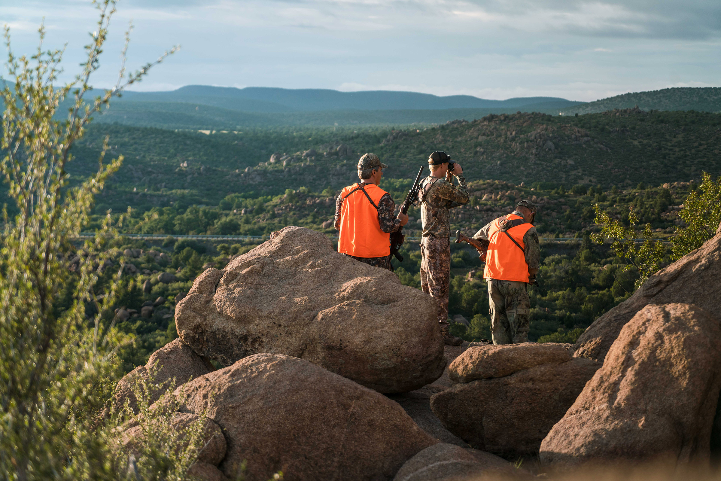 Three hunters on a boulder, holding guns